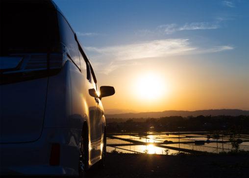 水田に反射しながら沈む夕日と自動車の写真素材