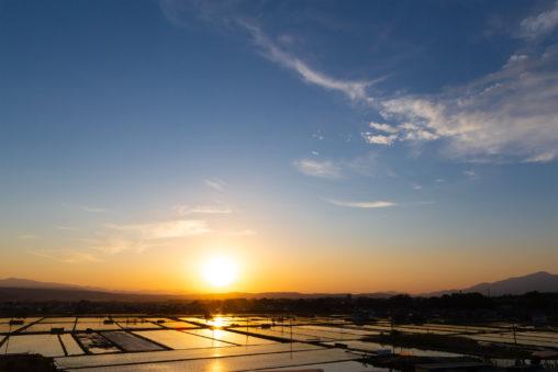 水田に反射しながら沈む夕日02の写真素材