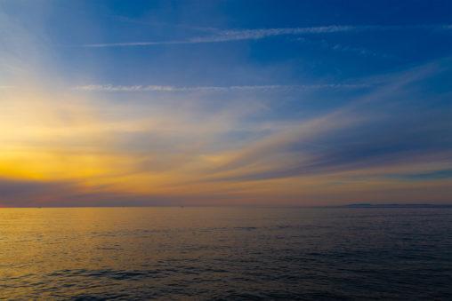 日本海と夕焼けと青空の写真素材