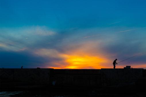釣り人と夕焼けの写真素材
