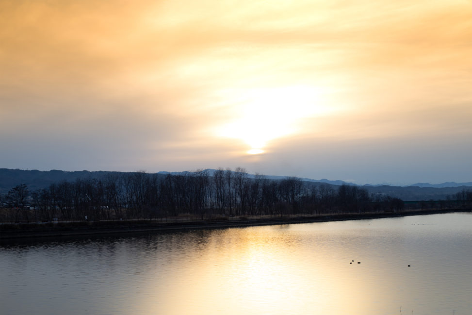 湖に反射する夕日(夕焼け)の写真素材