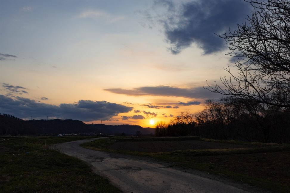 田舎道と夕日(夕焼け)の写真素材