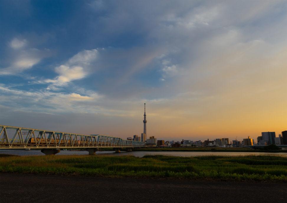 夕方の鉄橋を走る電車とスカイツリー02の写真素材
