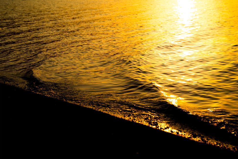 夕日に照らされた湖の波のフリー写真素材