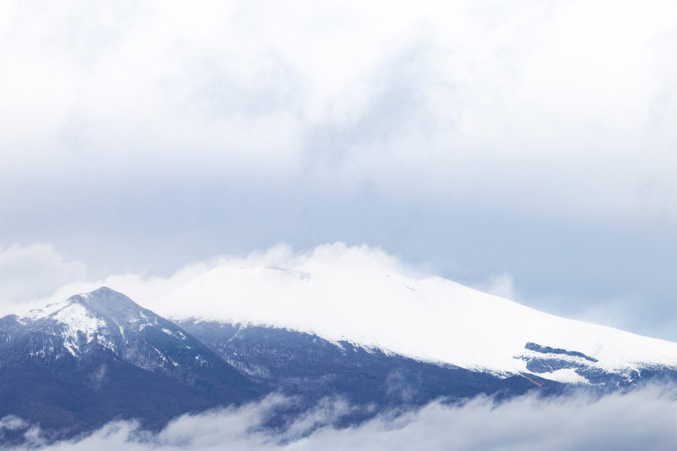 雲と雪が積もった浅間山のフリー写真素材