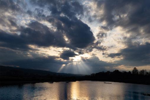 雲間からこぼれる薄明光線と湖のフリー写真素材