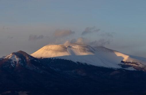 夕日に照らされる雪の浅間山の写真