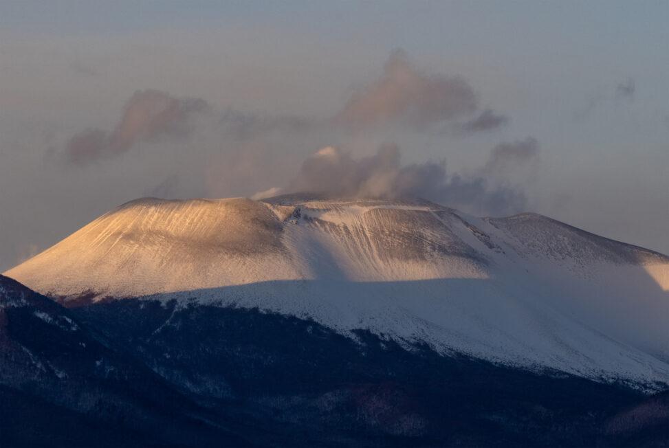 夕日に照らされる雪の浅間山(アップ)の写真